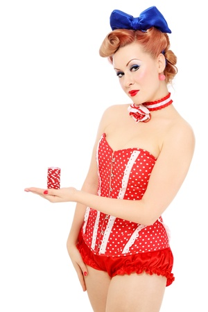 Young beautiful promo pin-up girl in vintage polka dot corset with red dice in hand over white background, copy space photo