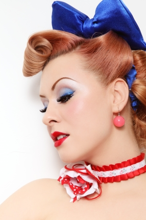 pinup: Portrait of beautiful young sexy pin-up girl with sparkly make-up and vintage hairstyle, over white wall