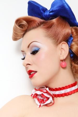 Ritratto di giovane e bella sexy pin-up girl con acconciatura sparkly make-up e vintage, su bianco muro