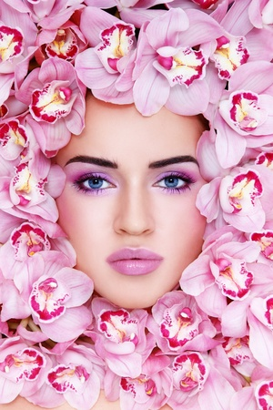 Portrait of beautiful woman with stylish make-up and pink orchids around her face photo