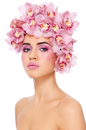 Young beautiful tanned sexy woman with fresh make-up and orchids in her hair over white background photo