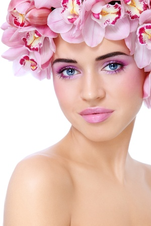 Young beautiful tanned sexy woman with fresh make-up and orchids in her hair, on white background Stock Photo - 13425962