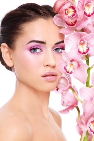 cejas: Joven hermosa mujer morena, con demasiado maquillaje y hermosa orqu�dea rosa, sobre fondo blanco