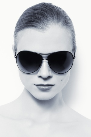 Portrait of young woman in stylish sunglasses over white wall photo