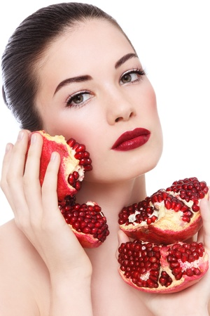 Portrait of young beautiful woman with pomegranates in her hands, on white background photo