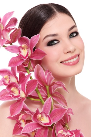 Young beautiful happy smiling girl with orchid on white background Stock Photo
