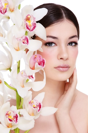Young beautiful healthy girl with orchid on white background photo
