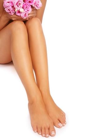 depilacion con cera: Pies y piernas de la mujer bronceada con flores de color rosa sobre fondo blanco