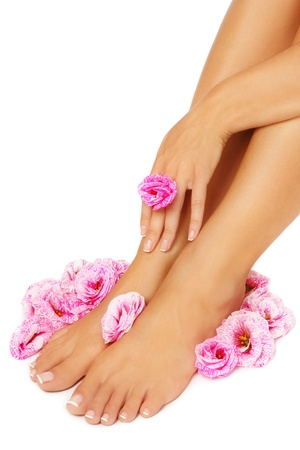manicure and pedicure: Feet and hand of tanned woman with pink flowers around, on white background