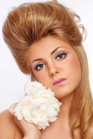 Young beautiful woman with stylish make-up and hairdo holding white flower in her hand photo