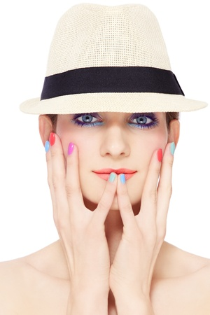 Portrait of young pretty girl in vintage hat, with bright make-up and colorful nail polish, on white background