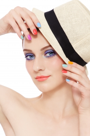 Portrait of young pretty girl in hat, with bright make-up and colorful nail polish, on white background
