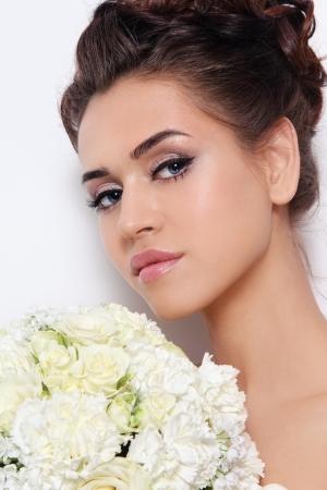 Schöne Braut mit stilvollen Make-up und Frisur hält Blumenstrauss in der Hand, über weiße Wand