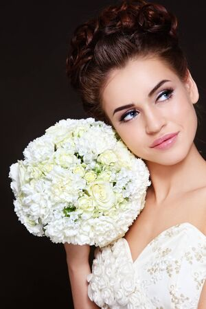 bridal makeup: Portrait of young beautiful bride with stylish make-up and hairdo holding bouquet in her hand Stock Photo