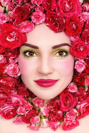 Portrait of young beautiful happy smiling woman with roses around her face photo