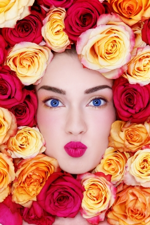 Portrait of young beautiful blue-eyed woman with funny expression and colorful roses around her face photo