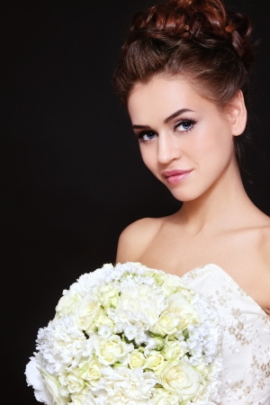 bridal makeup: Young beautiful bride with stylish make-up and hairdo holding bouquet in her hand