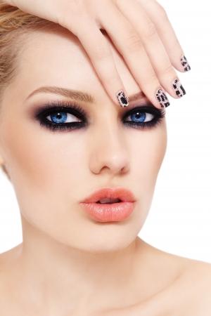 smoky eyes: Close-up ritratto di giovane donna bella con gli occhi fumosi e manicure fantasia, su sfondo bianco