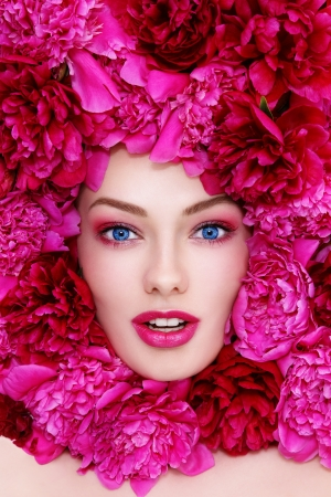 Portrait of young beautiful excited blue-eyed woman with pink peonies around her face photo
