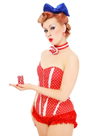 Young beautiful promo pin-up girl in vintage polka dot corset with red dice in hand over white background, copy space Stock Photo - 14496552