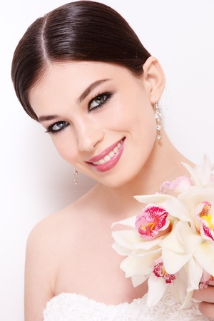 Portrait of young beautiful smiling bride with stylish make-up and orchid bouquet over white wall