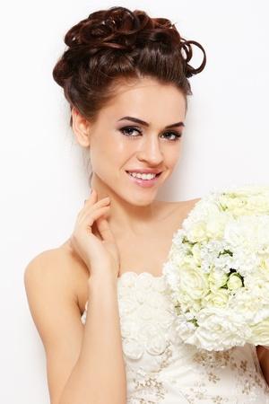 hairdo: Ritratto di giovane bella sposa sorridente, con elegante make-up e acconciatura su bianco muro