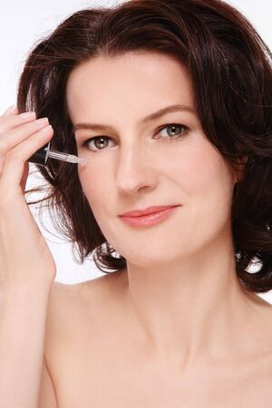 serum: Portrait of attractive groomed healthy middle-aged woman applying serum on her face Stock Photo