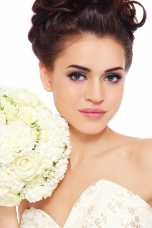 Portrait of young beautiful bride with stylish make-up and hairdo over white background photo