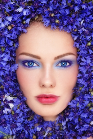 Cornflower: Close-up portrait of young beautiful blue-eyed woman with bluettes around her face Stock Photo