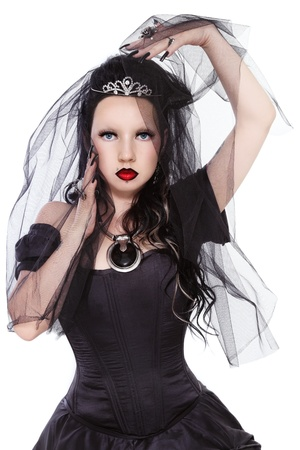 Young beautiful gothic woman in corset dress and black bridal veil over white background photo