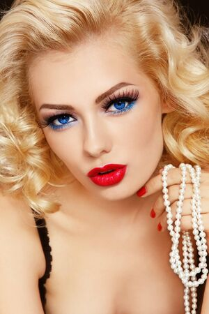 Young beautiful woman with blond curly hair holding pearls in her hand photo