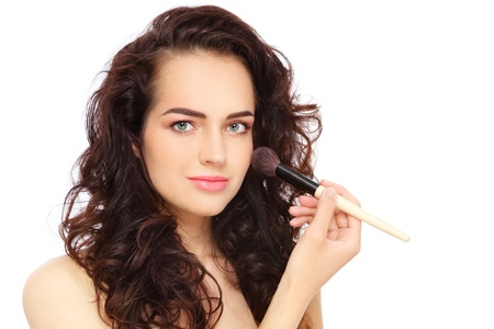 Young beautiful woman applying make-up with big brush, over white background photo