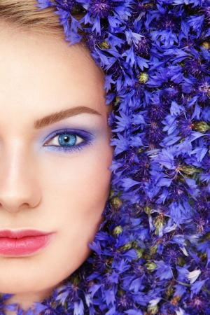 Close-up portrait of young beautiful blue-eyed woman with blue flowers around her face Stock Photo - 14642419