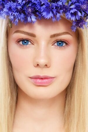 Close-up portrait of young beautiful blond woman with clear make-up and blue flowers Stock Photo - 14642415
