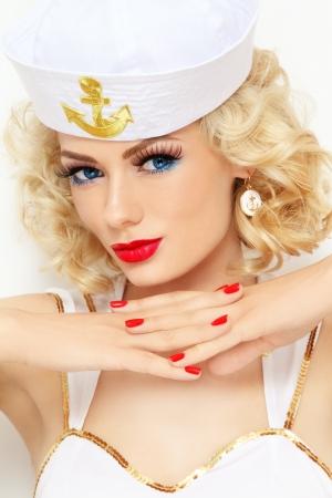 금발 곱슬 머리와 선원 옷을 입고 세련된 메이크업 젊은 아름 다운 섹시 한 여자