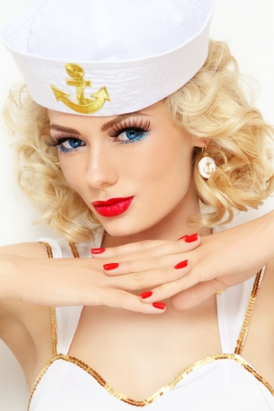 burlesque: Young beautiful sexy girl with blond curly hair and stylish make-up dressed as sailor