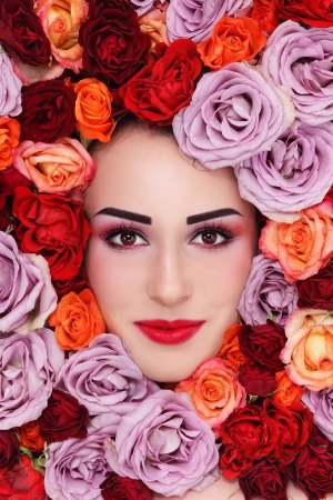 Portrait of young beautiful woman with stylish make-up and colorful roses around her face photo