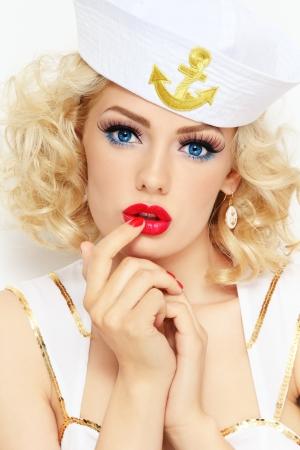 sailor: Joven hermosa chica sexy con el pelo rubio rizado y elegante maquillaje, vestido de marinero