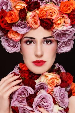 Junge schöne Frau mit stilvollen Make-up und bunten Rosen um ihr Gesicht