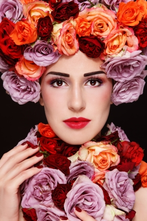 Young beautiful woman with stylish make-up and colorful roses around her face