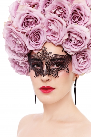 Young beautiful woman with fancy wig of roses and mask, on white background photo