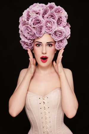 Young beautiful slim woman in corset with fancy wig of roses on her head and surprised expression photo