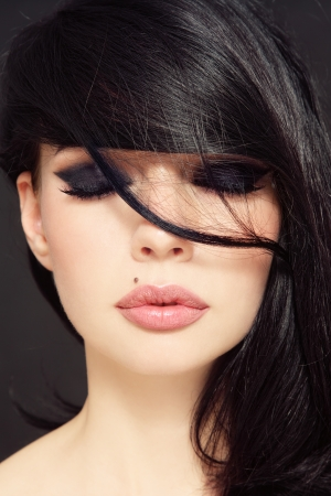 그녀의 얼굴에 긴 검은 머리를 가진 아름 다운 여자의 근접 초상화 스톡 콘텐츠