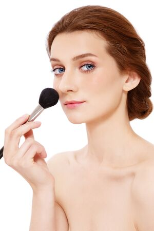 Young beautiful woman applying make-up with big brush, over white background Stock Photo - 15032578