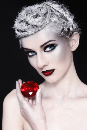 alien women: Portrait of young woman with fancy make-up and red gem in hand