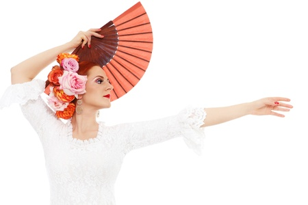 carmen: Young attractive flamenco dancer with roses in her hair and fan over white background