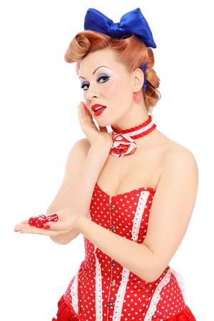 burlesque: Young beautiful promo pin-up girl in vintage polka dot corset with red dice in hand over white background
