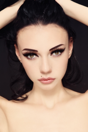 Portrait of young beautiful woman with stylish make-up touching her hair photo
