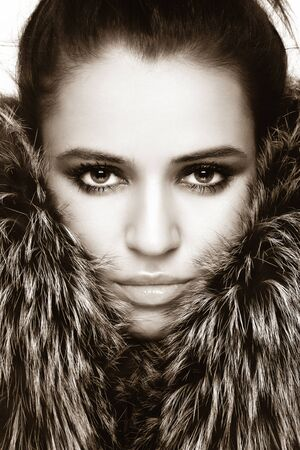 Close-up sepia portrait of young beautiful woman with stylish make-up and fur around her face photo