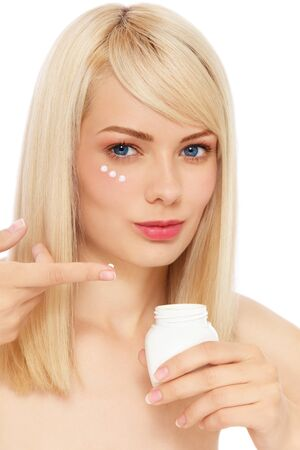 free radicals: Portrait of young fresh beautiful healthy woman applying cream on her face, over white background
